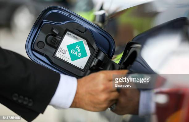 A driver removes the cap from a Mirai hydrogen fuel powered automobile manufactured by Toyota Motor Corp at Royal Dutch Shell Plc's first UK hydrogen...