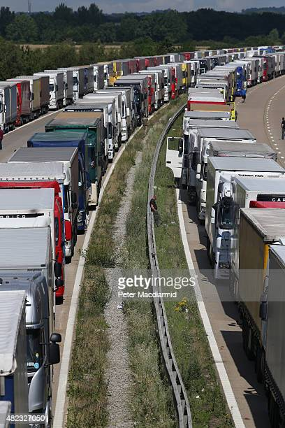 A driver rests on the central reservation as trucks line up on the M20 during Operation Stack on July 30 2015 near Ashford England Operation stack...