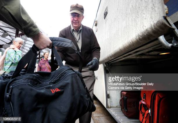 RTD driver Richard Bostwick right grabs a bag from a traveller to load under the bus while Amy Stiber left and Ellen Erhard center wait their turn on...