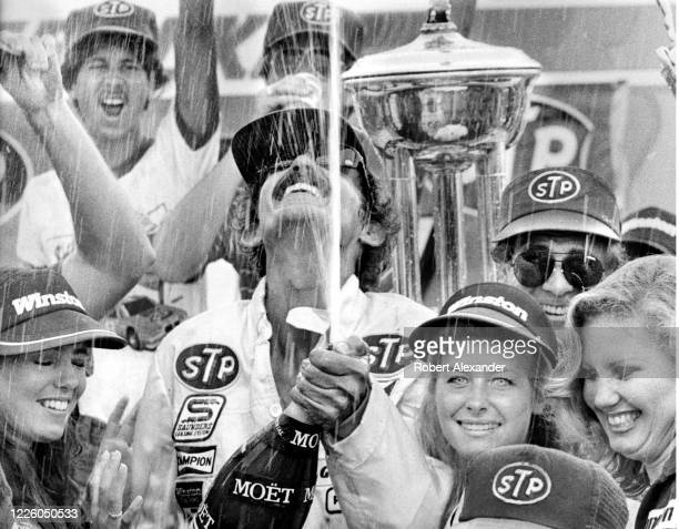 Driver Richard Petty opens the traditional winner's champagne bottle in Victory Lane after winning the 1984 Firecracker 400 stock car race at Daytona...