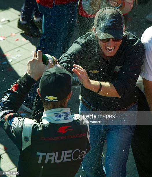 TORONTO ON JULY 13 Driver Sebastian Bourdais doses his boss Jay Penske with champagne as they celebrate his 3rd place finish Toronto Honda Indy...