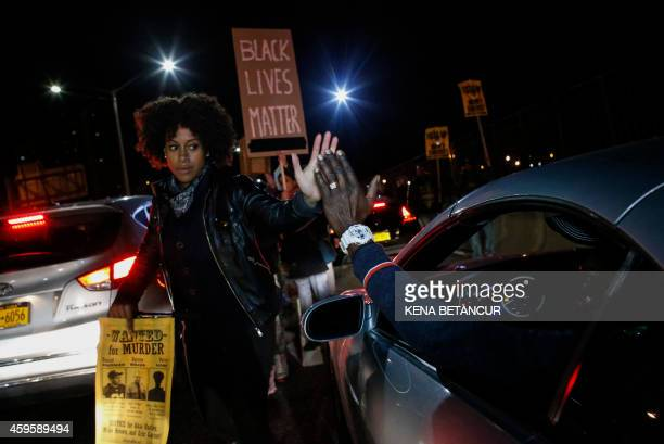 A driver shakes hands with a demonstrator during a protest march along FDR drive on November 25 2015 in New York City one day after a grand jury...