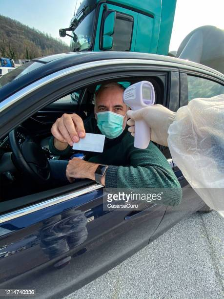 driver showing id at border control with body temperature measurement during covid-19 crisis - infrared thermometer stock pictures, royalty-free photos & images