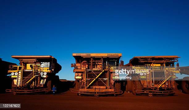 Driver stand by a row of Komatsu Ltd. Haul trucks at Sishen open cast mine, operated by Kumba Iron Ore Ltd., an iron ore-producing unit of Anglo...