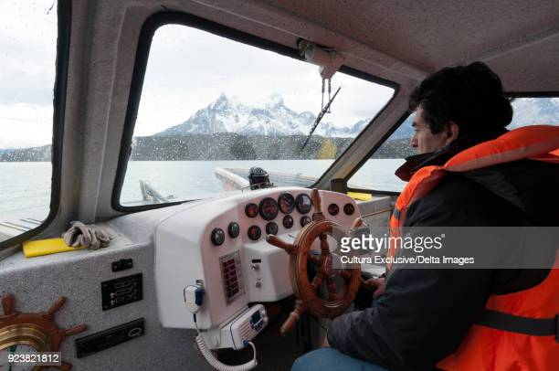 Driver steering boat, Lago Pehoe, Torres del Paine National Park, Patagonia, Chile