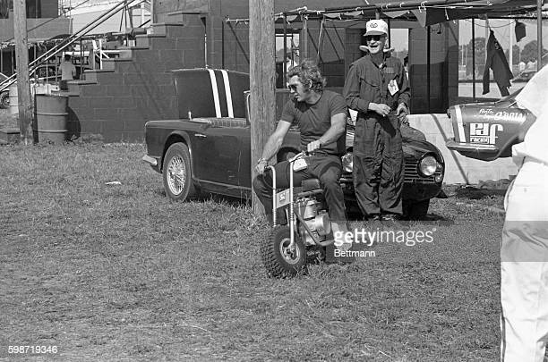 Driver Steve McQueen gets the pit crews laughing as he spins around on a minibike with his leg in a cast The Los Angeles based driver broke his foot...