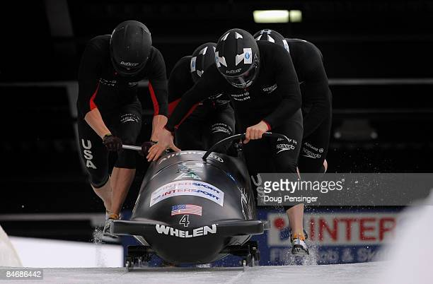 Driver Steven Holcomb of the USA and his crew push from the start on their first run as they finished second in the men's four man bobsleigh finals...