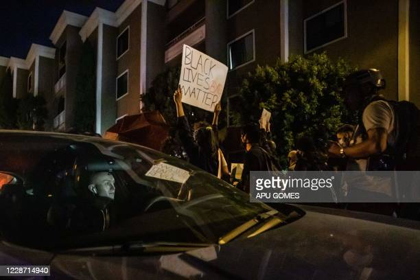 A driver stuck in the protest watches demonstrators passing by his car as they manifest their discontent over the lack of criminal charges in the...