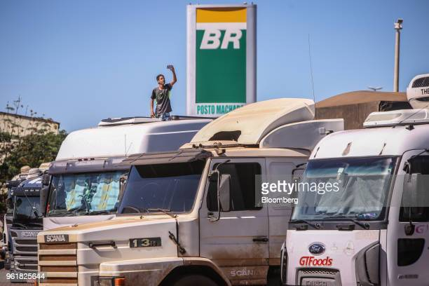 A driver takes a photograph of trucks parked at a Petroleo Brasileiro SA gas station near on BR 040 highway during a protest against rising fuel...
