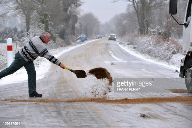 A driver throws sand near the tires of his truck on a ice covered road on January 18 2013 near VigneuxdeBretagne Brittany western France Thirtyseven...