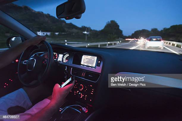 A Driver Uses A Cell Phone While Driving At Dusk