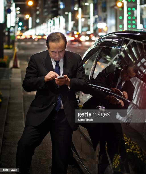 Driver uses his mobile phone to look for directions in Ginza, Tokyo at night