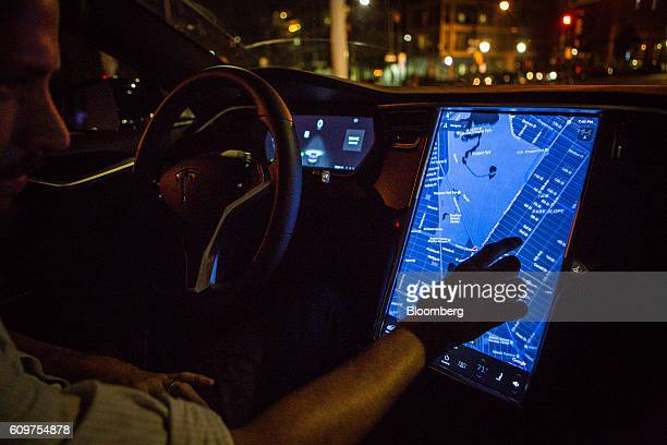 A driver uses the map navigation feature on a touchscreen control panel with the Tesla Motors Inc 80 software update inside a Tesla Model S P90D...