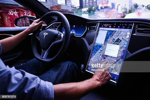 A driver uses the map navigation feature on a touchscreen control panel just prior to the Tesla Motors Inc 80 software update inside a Model S P90D...