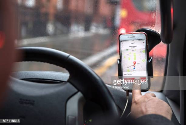 A driver uses the Uber Technologies Inc ridehailing service smartphone app to complete passenger dropoff in this arranged photograph in London UK on...