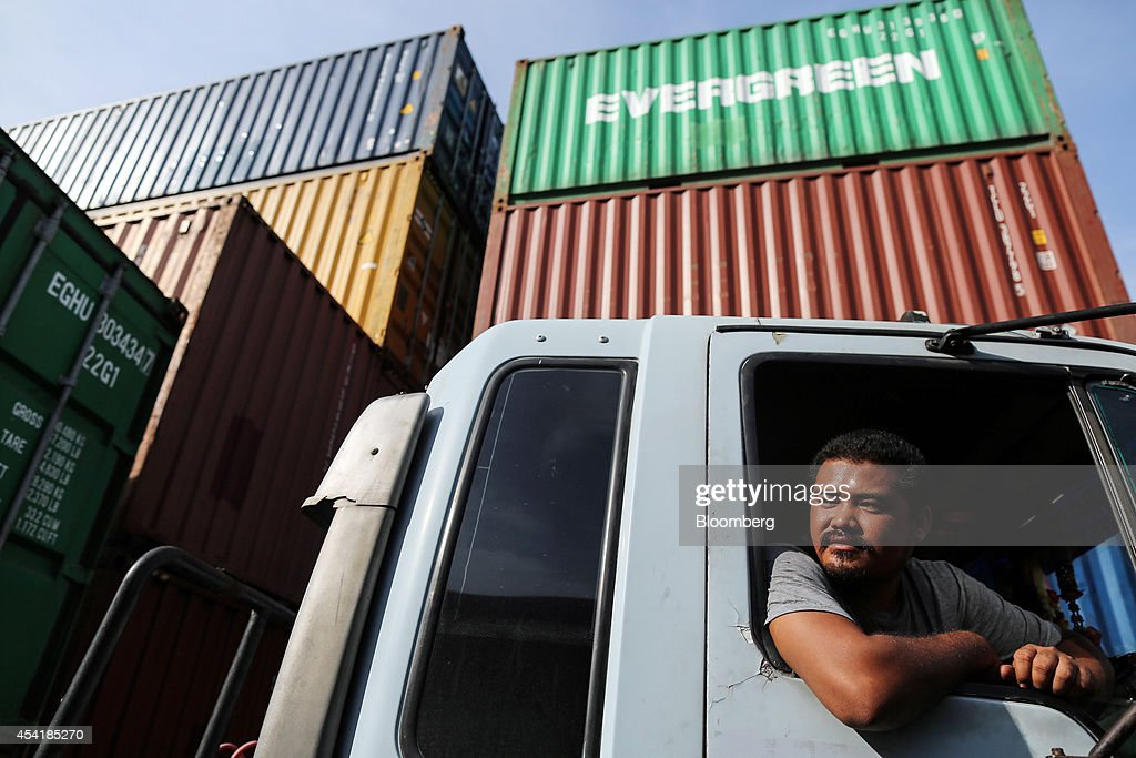 A driver waits to maneuver his truck while parked next to stacked containers at the Custom Global Service Co. container depot in Bangkok, Thailand, on Monday, Aug. 25, 2014. Thailand's trade figures are scheduled for release on Aug. 27. Photographer: Dario Pignatelli/Bloomberg via Getty Images