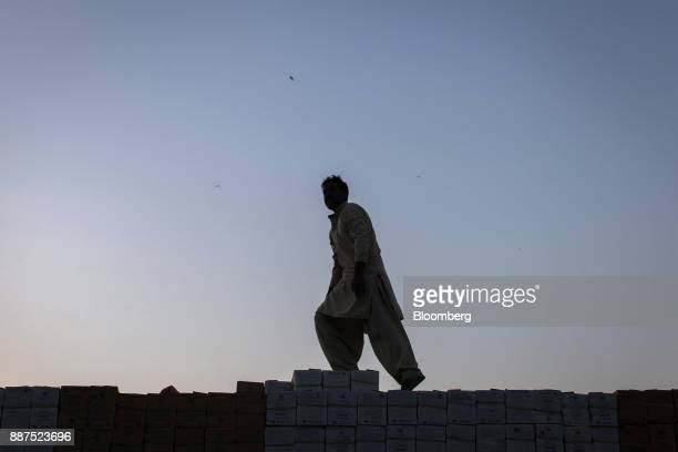 A driver walks across boxes of tiles stacked on a truck at the Shabbir Tiles Ceramics Ltd production facility at dusk in Karachi Pakistan on...