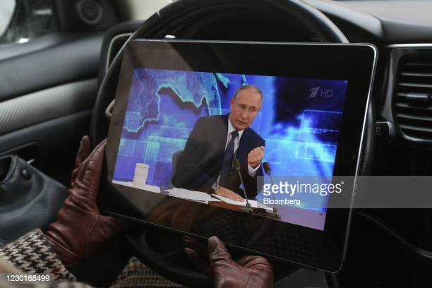 Driver watches a live broadcast of Vladimir Putin, Russia's President, delivering his annual news conference on an Apple Inc. IPad in Moscow, Russia,...