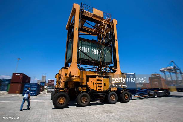 A driver watches as a straddle carrier drops a China Shipping Container Lines Co branded container onto a truck for distribution from Limassol port...