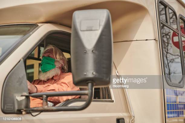 A driver wears a protective mask while driving in Sioux Falls South Dakota US on Wednesday April 15 2020 South Dakota Governor Kristi Noem has argued...