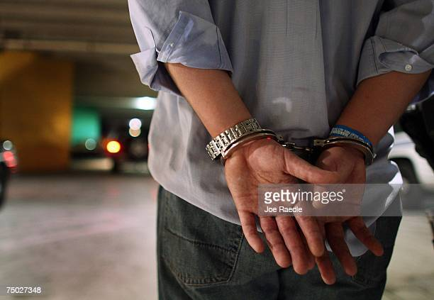 A driver who failed a field sobriety test at a DUI traffic checkpoint stands in handcuffs waiting to be processed June 4 2007 in Miami Florida...