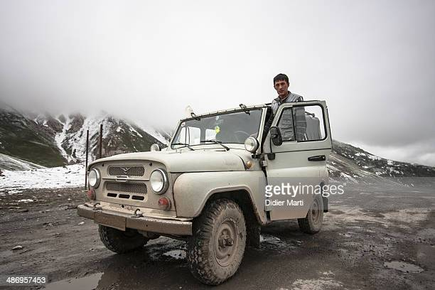 Driver with his UAZ in the mountains along the Pamir Highway in Kyrgyzstan