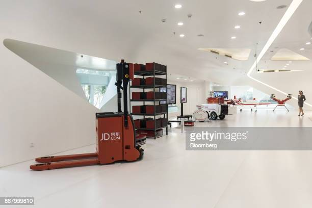 A driverless forklift left and other unmanned automated guided vehicles for loading and unloading goods stand on display at a showroom inside the...