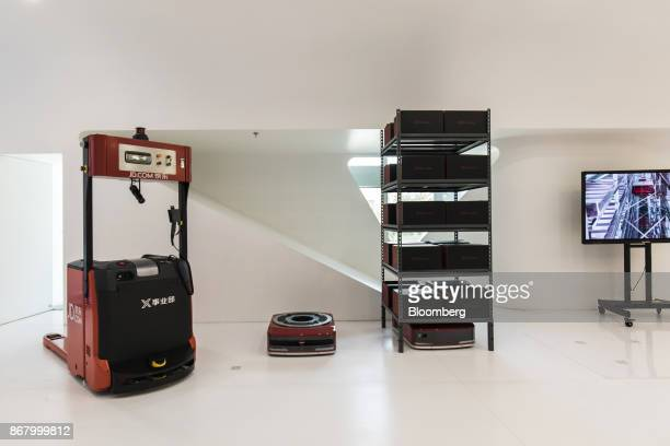 A driverless forklift left and unmanned automated guided vehicles for loading and unloading goods stand on display at a showroom inside the JDcom Inc...