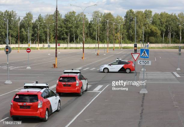 Driverless Toyota Motor Corp Prius hybrid cars operated by YandexTaxi part of YandexNV wait at a junction during a selfdriving taxi trial on a test...