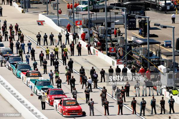Drivers and crew stand during the national anthem prior to the NASCAR Gander Outdoors Truck Series South Carolina Education Lottery 200 at Darlington...