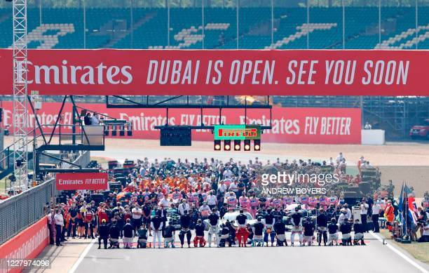 Drivers and team members stand on the grid ahead of the F1 70th Anniversary Grand Prix at Silverstone on August 9, 2020 in Northampton. - This...
