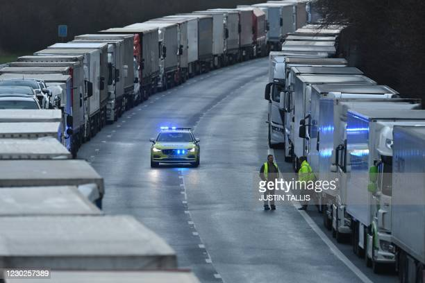 Drivers are seen on the road as a police car approaches as freight lorries and goods vehicles queue on a closed section of the M20 motorway which...