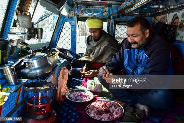 Drivers are seen preparing food in their truck carrying essential supply on a closed National Highway in Qazigund about 85kms from Srinagar Indian...