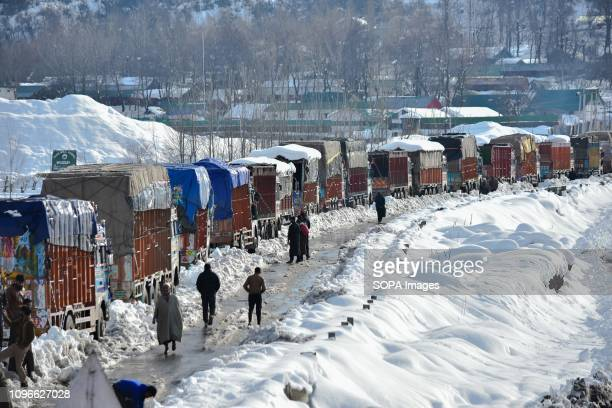 Drivers are seen waiting next to their stranded trucks carrying essential supply on a closed National Highway in Qazigund about 85kms from Srinagar...