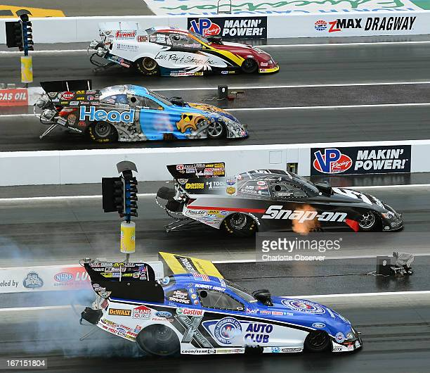 Drivers compete in a Funny Car qualifying race during the 2013 Dollar General NHRA FourWide Nationals at zMax Dragway in Concord North Carolina on...