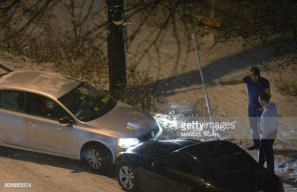 Drivers confer outside of their cars after a collision on January 20 2016 in Washington DC The region received a light snowfall ahead of the expected...