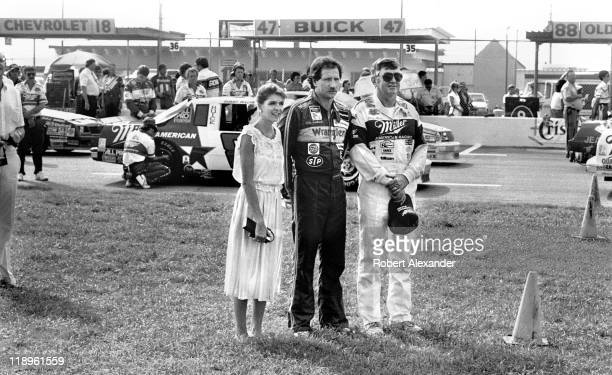 NASCAR drivers Dale Earnhardt and Bobby Allison and Earnhardt's wife Teresa stand near the race cars during opening ceremonies for the 1986...