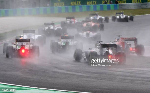 Drivers exit the first corner during the Hungarian Formula One Grand Prix at Hungaroring on July 27 2014 in Budapest Hungary