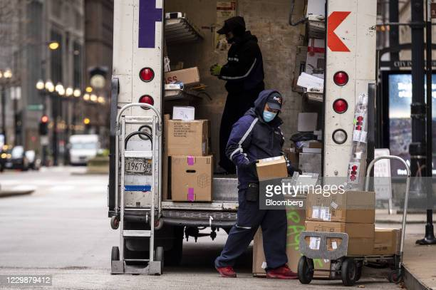 Drivers for an independent contractor to FedEx Corp. Wearing protective masks unload a Ground truck in Chicago, Illinois, U.S., on Monday, Nov. 30,...