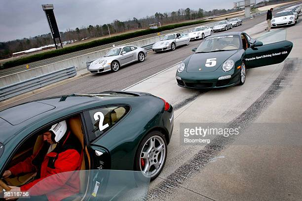 Drivers get into their Porsche 911 Carrera vehicles during a Porsche Sport Driving School Masters Plus race license course event at Barber...