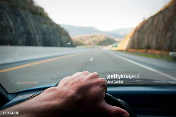 Driver's hand on the wheel driving down highway