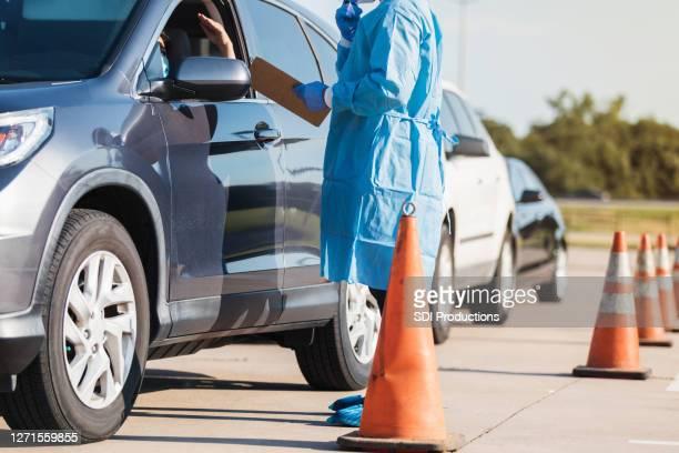 車のドライバーはcovid-19テストのために並ぶのを待ちます - ドライブスルー検査 ストックフォトと画像