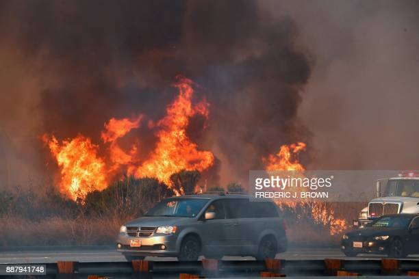 Drivers in their vehicles make their way past a raging fire on the side of the US 101 freeway at the beachside community of Faria Beach northwest of...