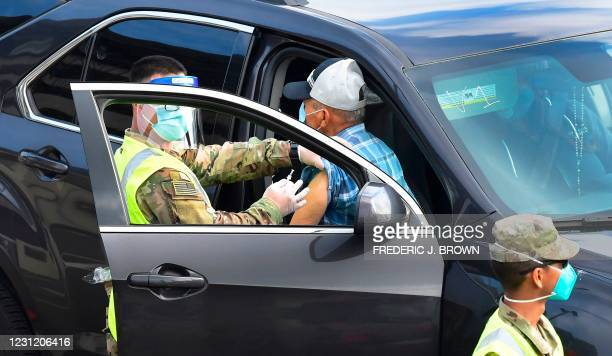 Drivers in vehicles arrive for their Covid-19 vaccinations administered by members of the National Guard on the opening day of a new mass Covid-19...
