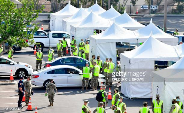 Drivers in vehicles pull up toward white tents for Covid-19 vaccinations administered by members of the National Guard on the opening day of a new...