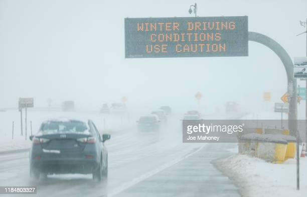 Drivers make their way along slick and snowy roads on November 26 2019 in Denver Colorado A strong winter storm dropped nearly a foot of snow on the...