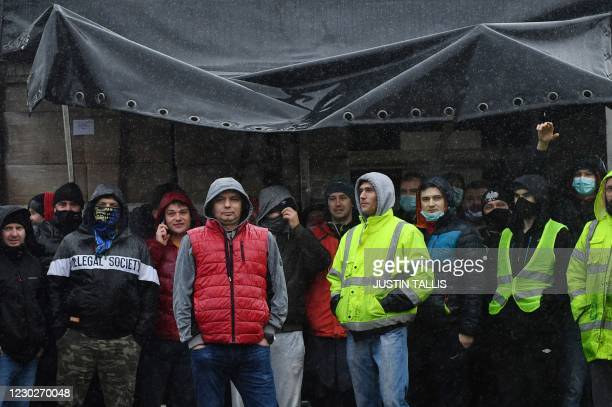 Drivers not being allow entry to the port of Dover shelter from the rain by a lorry as they block the road access to the port in Dover, in Kent,...