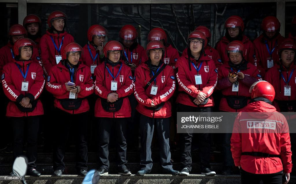Drivers of Baidu's food delivery service line up for the morning roll call in Shanghai on March 15, 2016. / AFP / JOHANNES