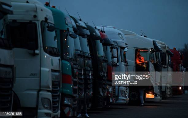 Drivers of freight lorries and heavy goods vehicles are illuminated by the lights inside their cabs as they are parked at a truck stop off the M20...