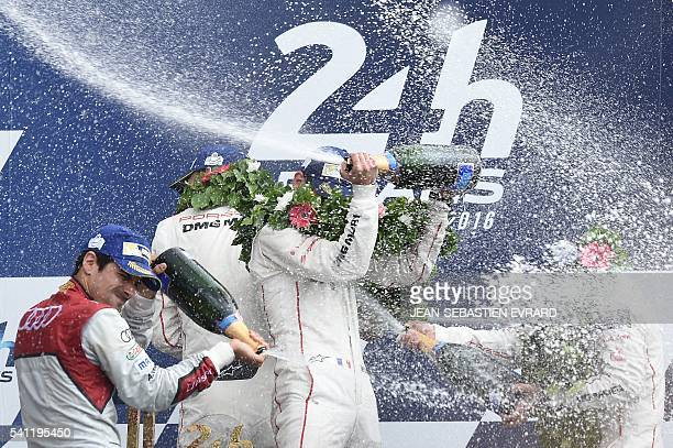 Drivers of the Porsche 919 Hybrid N°2 Germany's Marc Lieb France's Romain Dumas and Switzerland's Neel Jani spray champagne as they celebrate on the...